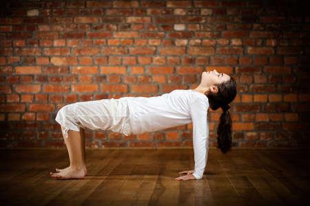 Woman exercising yoga against brick wall Stock Photo - 17993500