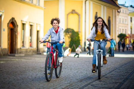 Urban biking - teens riding bikes in city photo