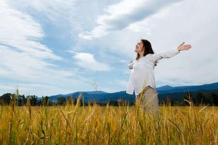 Meisje bedrijf armen omhoog tegen de blauwe hemel Stockfoto