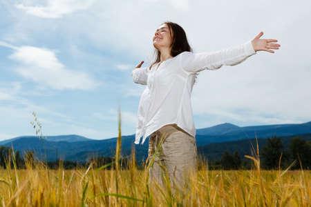 alabanza: Muchacha que sostiene los brazos hacia arriba contra el cielo azul
