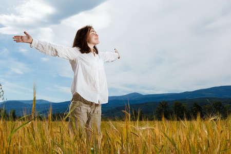 praise: Muchacha que sostiene los brazos hacia arriba contra el cielo azul
