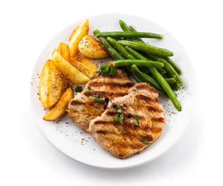 Gegrilde steaks, gebakken aardappelen en groenten Stockfoto