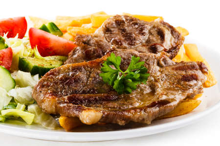Grilled steaks, French fries and vegetables Stock Photo - 18422363