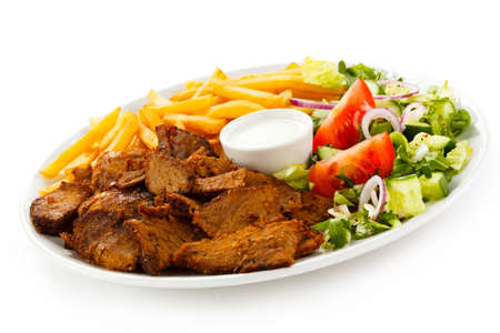 Grilled meat with French fries and vegetables