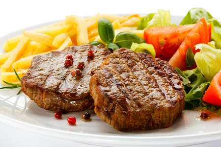 loin chops: Grilled steaks, French fries and vegetables
