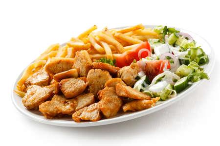 pinchos morunos: Carne a la brasa con patatas fritas y verduras Foto de archivo