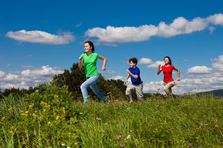 sporting activity: Active family - mother and kids running, jumping outdoor Stock Photo