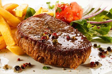 Grilled steaks, French fries and vegetables Reklamní fotografie