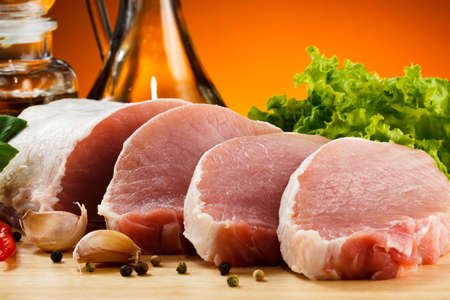 loin chops: Raw pork on cutting board and vegetables