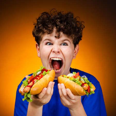 perro caliente: Muchacho que come s�ndwiches grandes Foto de archivo