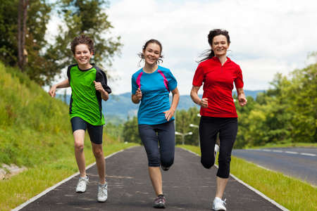 madre e hija adolescente: Activo familia - madre y los niños corriendo al aire libre