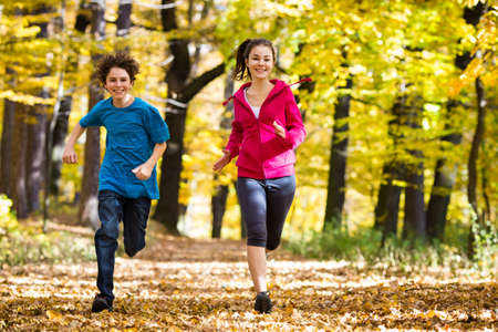 sporting: Girl and boy running, jumping in park
