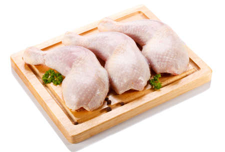 Raw chicken legs on cutting board on white background photo