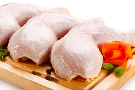 raw chicken: Raw chicken legs on cutting board on white background