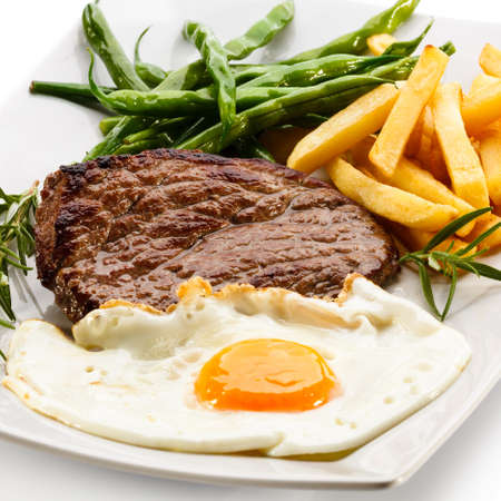 loin chops: Grilled steaks, French fries, fried egg and vegetables