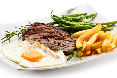 chicken or egg: Grilled steaks, French fries, fried egg and vegetables