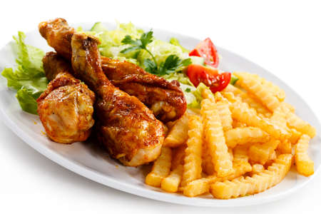 french fries plate: Grilled chicken legs with chips and vegetables