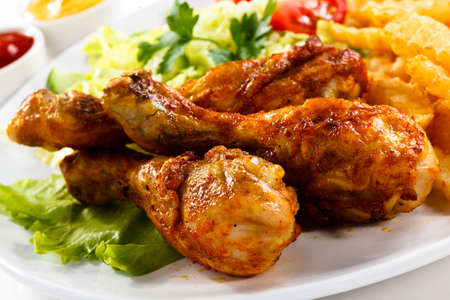 Grilled chicken legs with chips and vegetables photo