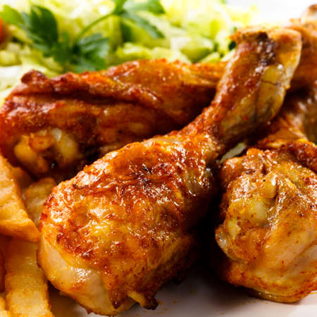 chicken leg: Grilled chicken legs with chips and vegetables