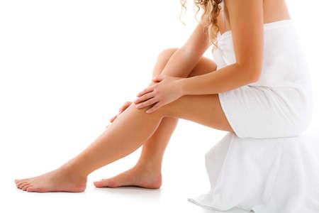 piernas mujer: Mujer delgada que se sienta en el fondo blanco Foto de archivo