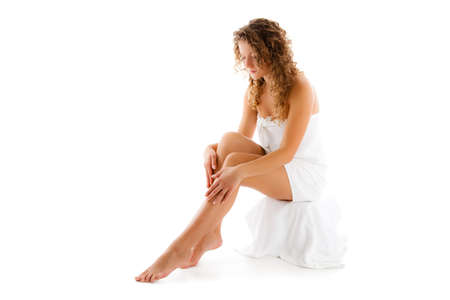 waxed legs: Slim donna seduta su sfondo bianco