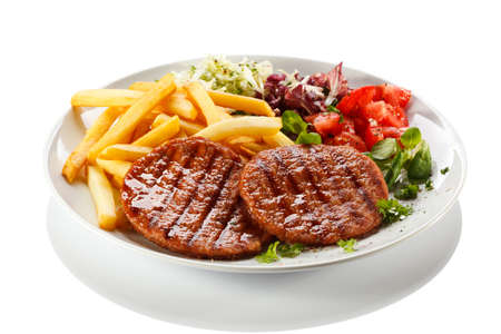 cutlets: Grilled steaks, French fries and vegetables