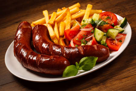 cooked sausage: Grilled sausages, French fries and vegetables