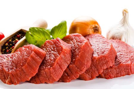 vlees: Rauw rundvlees en groenten op een witte achtergrond
