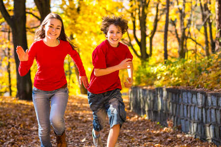 fall fun: Girl and boy running, jumping in park