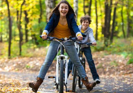 Urban biking - teens riding bikes in city park Stock Photo