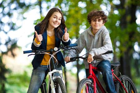 niños en bicicleta: Urban Biking - adolescentes andar en bicicleta en parque de la ciudad