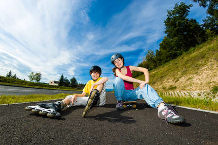 Active young people with roller skate and skateboard photo