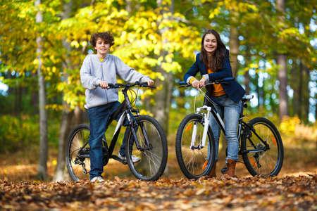 Urban biking - teens riding bikes in city park photo
