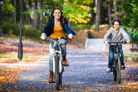 Urban biking - teens riding bikes in city park 版權商用圖片