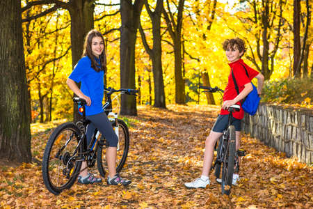 Urban biking - teens riding bikes in city park photo