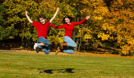 Girl and boy running, jumping in park photo