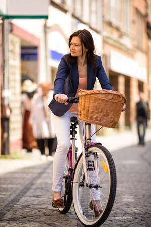 Urban biking - middle-age woman and bike in city photo