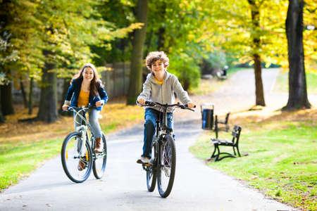 city bike: Urban biking - teens riding bikes in city park Stock Photo
