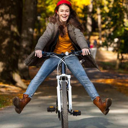 andando en bicicleta: Urban bike - chica y bicicleta en el parque de la ciudad Foto de archivo