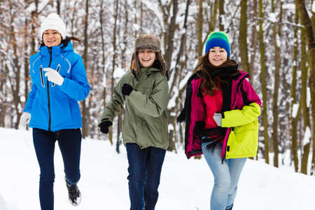 Active family - mother and kids running outdoor in winter park photo