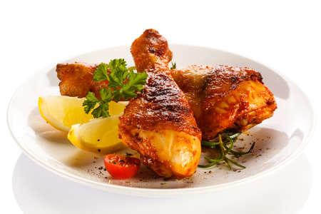 Gegrilde kip benen en fruit op een witte achtergrond Stockfoto