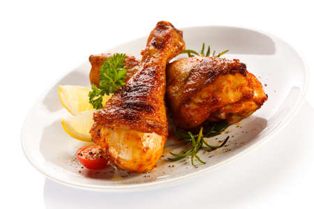 chicken leg: Grilled chicken legs and vegetables on white background