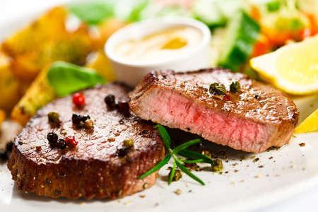 Gegrilde biefstuk, gebakken aardappelen en groenten Stockfoto
