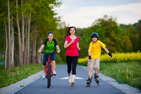Active family - mother and kids running, biking, rollerblading photo