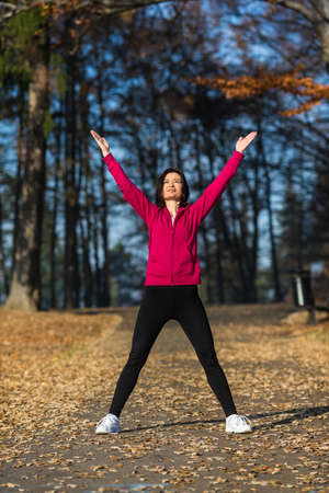 age 40 45 years: Woman exercising in park