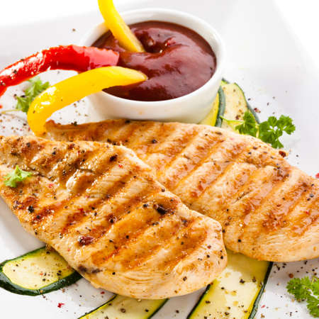 Grilled chicken breasts and vegetables photo