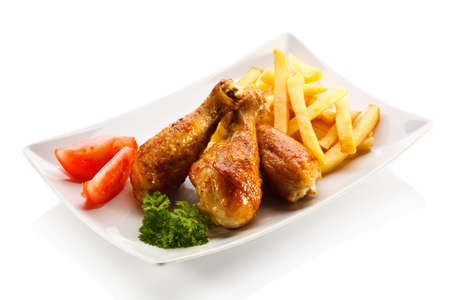 Grilled chicken drumsticks with chips and vegetables photo