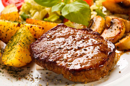 loin chops: Grilled steak, baked potatoes and vegetables