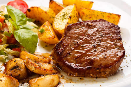 baked potatoes: Grilled steak, baked potatoes and vegetables