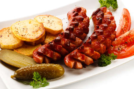 Grilled sausages, baked potatoes and vegetables photo
